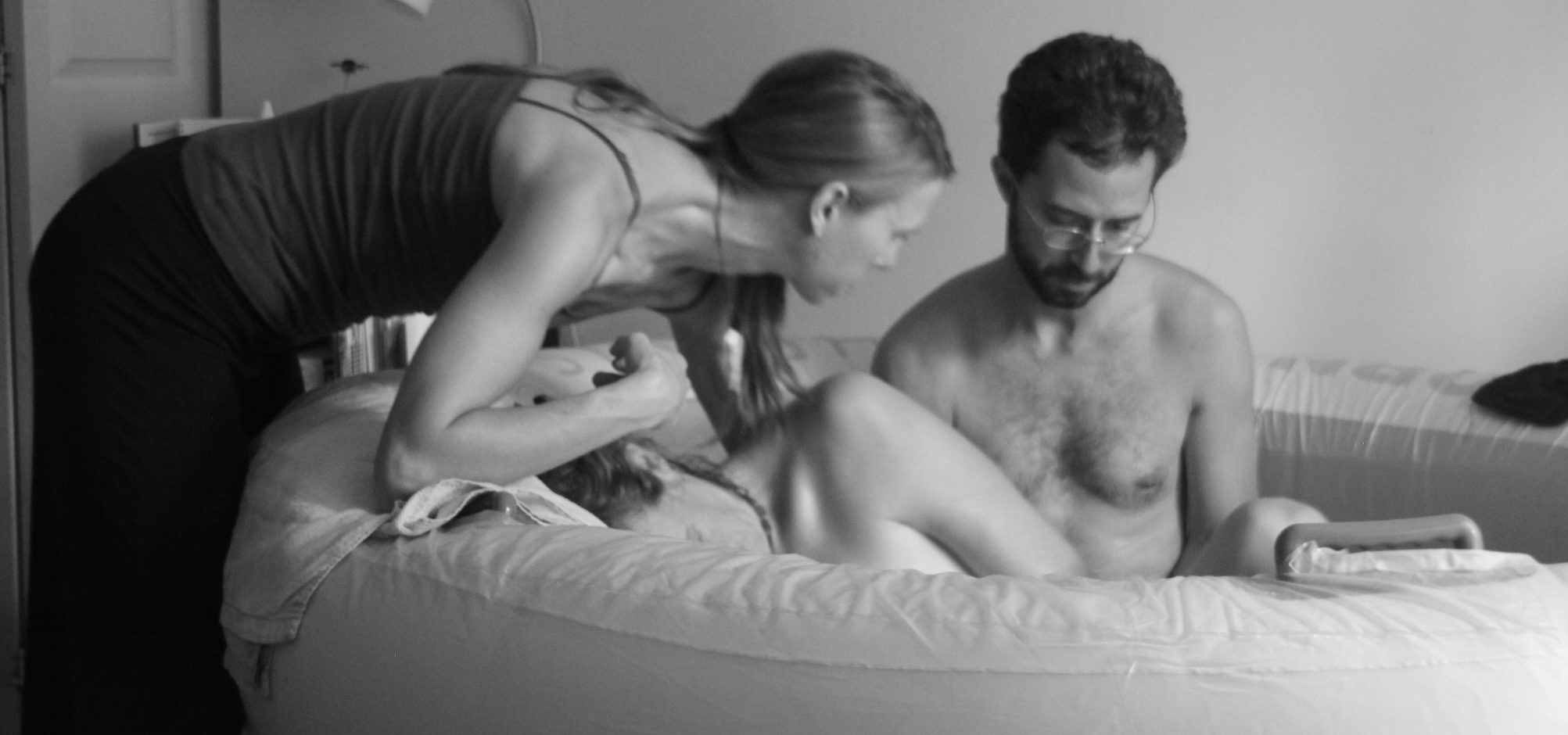Applying pressure to her lower back while she labors in the birth tub with her partner